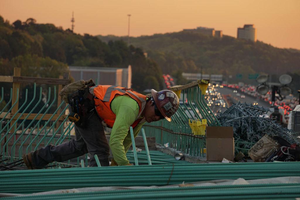En arbetare i varselkläder är på ett tak i skymningen
