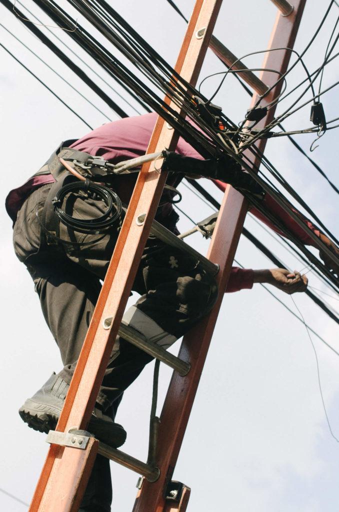 En arbetare i klättrar på en stege